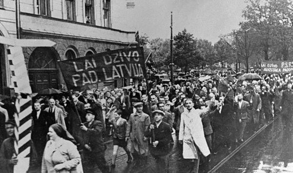 """Демонстранты, идущие по улицам Риги, несут транспаранты с надписью """"Да здравствует Советская Латвия"""", 1940 год"""