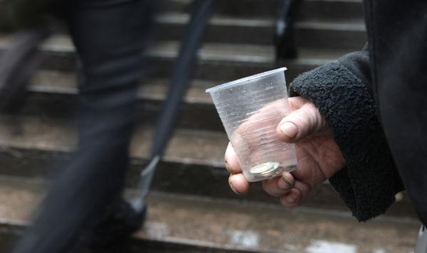 Деньги в пластиковом стакане в руке бедняка